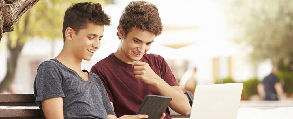 Teenager schauen auf Tablet und Laptop