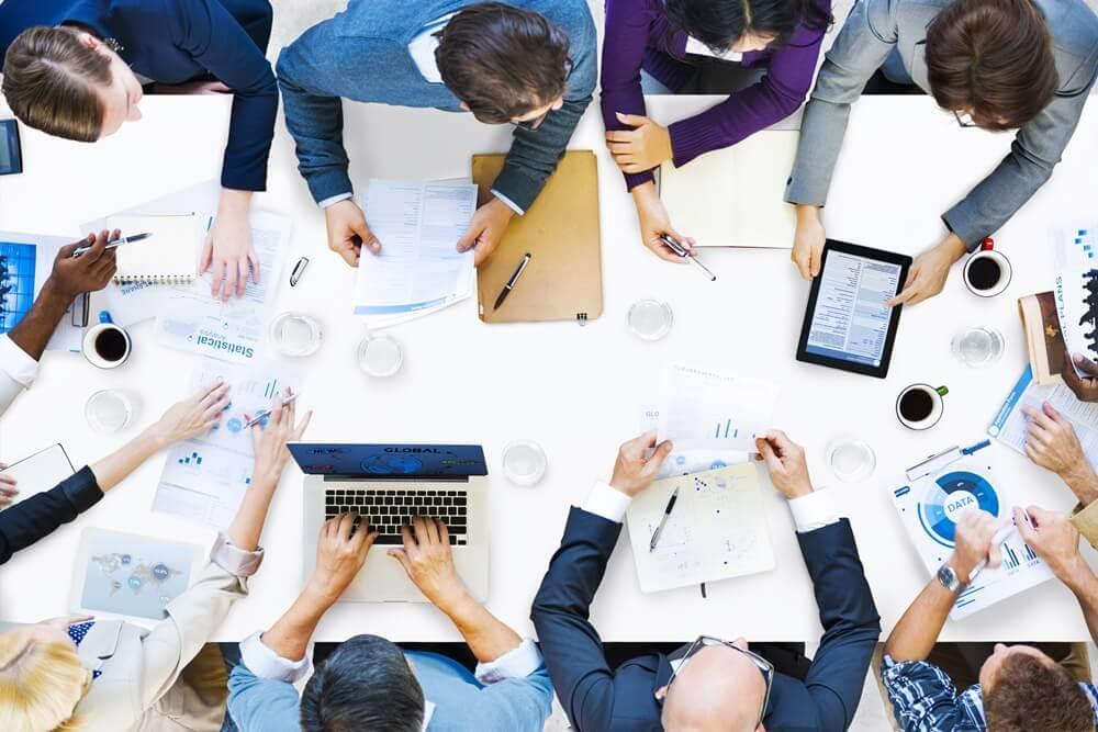 Arbeitsmeeting mit Laptops und Tablets