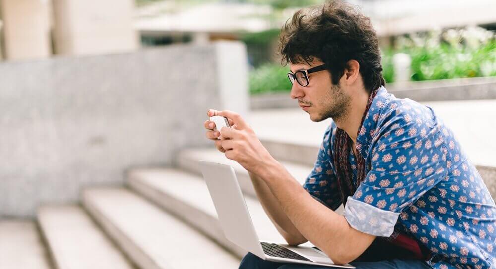 Junger Mann ließt auf Smartphone mit Laptop auf dem Schoß