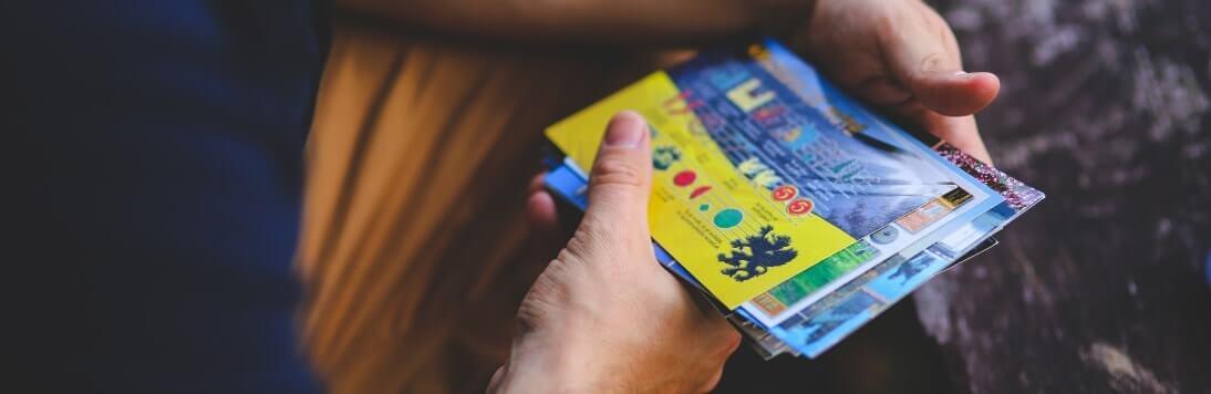 Mann hält Postkarten in den Händen
