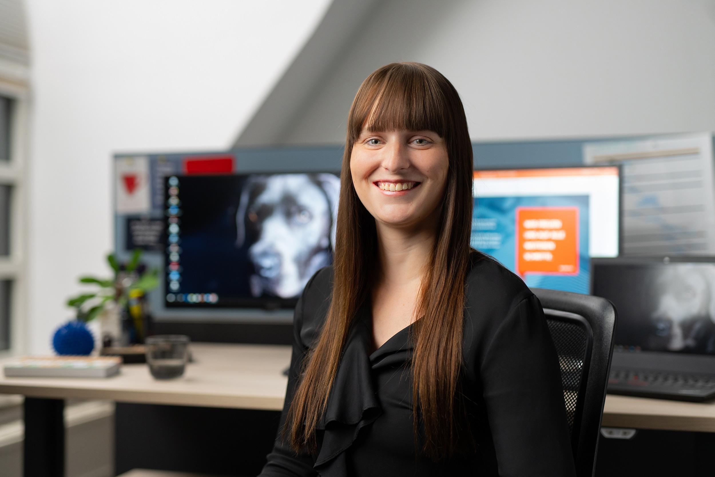 Portrait Mitarbeiterin vor Schreibtisch mit Monitoren